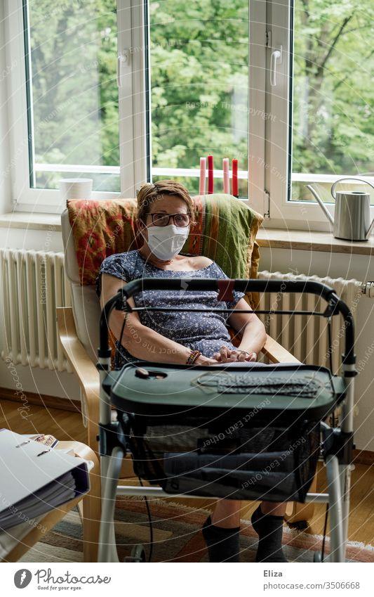 Frau der Risikogruppe mit Maske und Rollator sitzt aufgrund der Corona-Krise alleine zuhause in Isolation Covid-19 Mundschutz behindert Prävention Corona-Virus