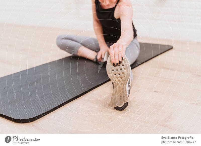 junge Frau, die sich nach dem Sport im Fitnessstudio dehnt. Gesunder Lebensstil Hanteln Frauen Freunde Gesundheit Lifestyle im Innenbereich Training schwer