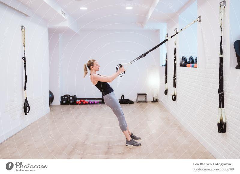 junge Frau, die im Fitnessstudio mit Trx Sport treibt. Gesunder Lebensstil Hanteln Frauen Freunde Gesundheit Lifestyle im Innenbereich Training schwer Pflege