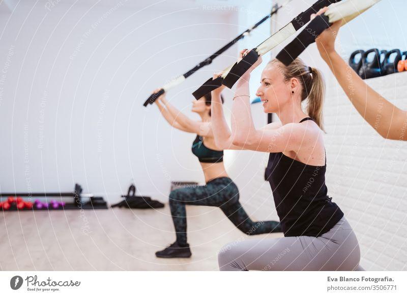Gruppe von Frauen, die in der Turnhalle mit Trx Sport treiben. Gesunder Lebensstil Hanteln Fitnessstudio Freunde Gesundheit Lifestyle im Innenbereich Training