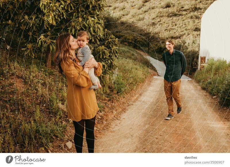 Eine Frau, die ihren kleinen Sohn in der Natur küsst, steht im Weg, während der Mann sich ihnen mit einem Lächeln nähert. Landschaft liebende Familie