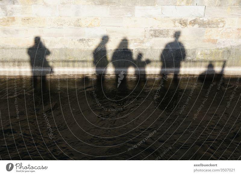 Schatten einer Menschengruppe versinken im Wasser Untergang Klimawandel Fluss Mauer dunkel abstrakt anders Hochwasser Flut Überschwemmung Umwelt Wetter metapher