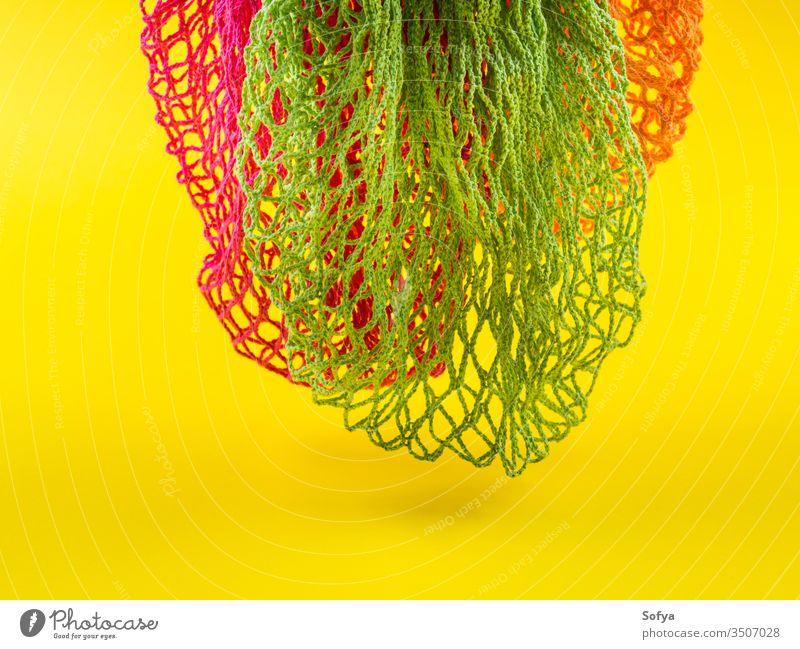 Wiederverwendbare Netzbeutel aus Baumwolle auf gelbem Hintergrund. wiederverwendbar keine Verschwendung farbenfroh Tasche kaufen ökologisch Farbe Konzept orange