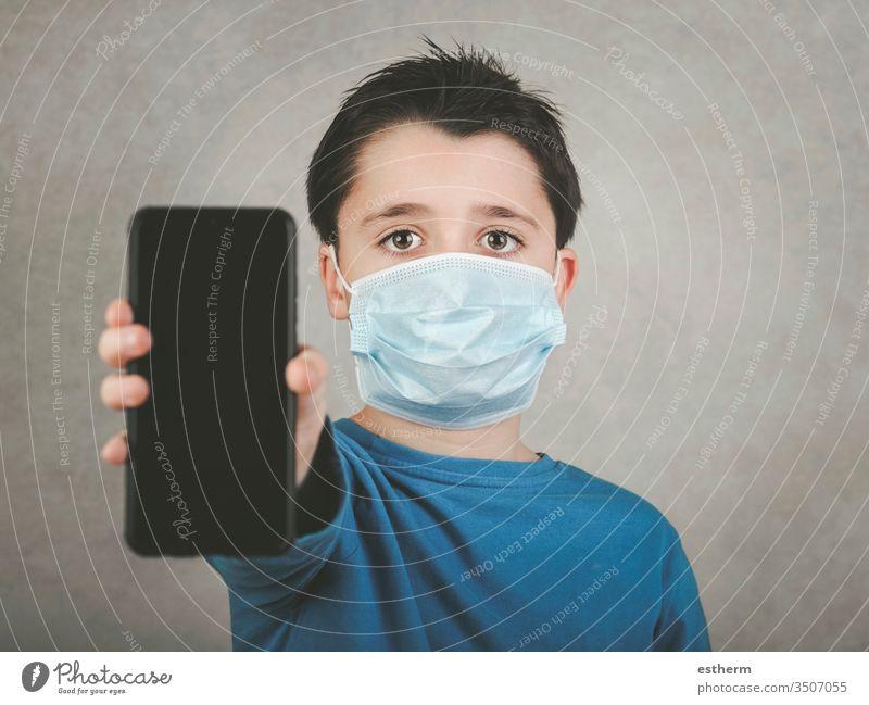 Kind mit medizinischer Maske und Smartphone Coronavirus Virus 2019-ncov Seuche covid-19 Pandemie Quarantäne Symptom Medizin digital Computer Mitteilung