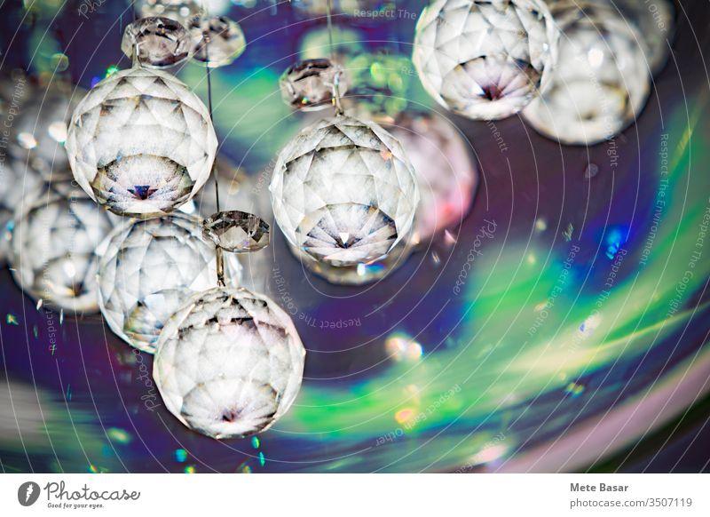 Hängende opake Kristallkugeln mit blau-grüner Hintergrundfarbe und zufälligen Fackeln. digital manipuliert undurchsichtig kristallisieren facettiert Bälle Saum