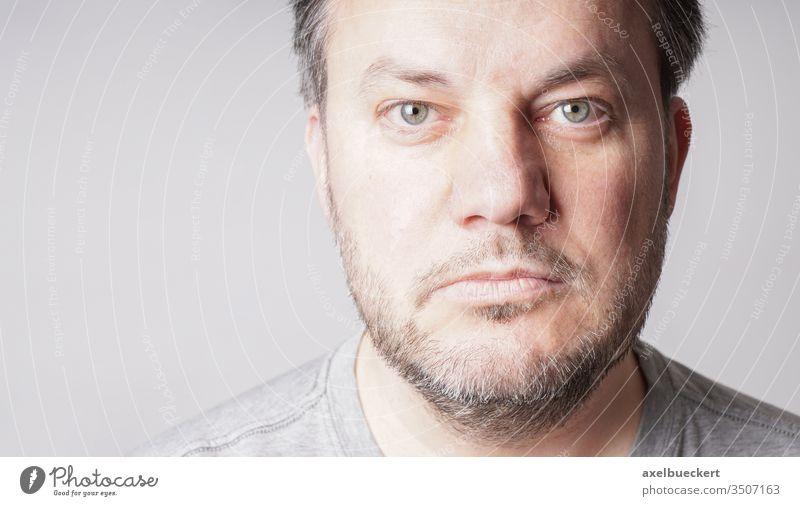erwachsener Mann schaut in die Kamera - Nahaufnahme mit Textfreiraum Porträt ernst Erwachsener Menschen grau Vollbart allein reif Lebensalter Alterung männlich