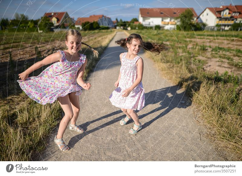 Two sisters play games summer sonne jumpin tanzen smiley happy schatten feld dorf girls kleid