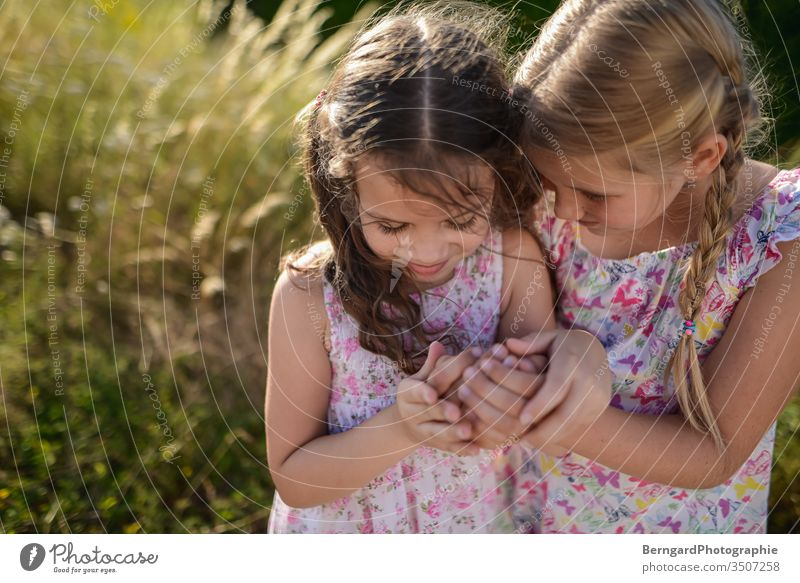 Two sisters play games sommer licht hair smile Geheimnis playtime hands girls