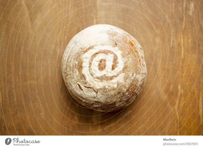 At-Zeichen mit Mehl auf einem Brot dekoriert brot Brotlaib backen bäcker bäckerei backware nahrungsmittel rund tisch vollkornbrot mehl Onlinehandel at-zeichen