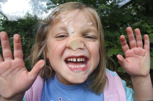 Kind hinter Glasscheibe Kindheit Spielen Freude platte Nase spass lustig Grimasse Grimassen schneiden Gesicht Mund Finger Zähne Zähne zeigen Fröhlichkeit frech