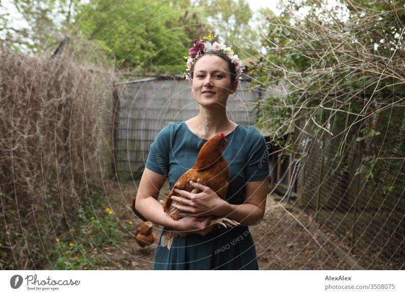 Junge Frau mit Blumenkranz im Haar steht im Hühnerauslauf hält braunes Huhn im Arm Zentralperspektive Schwache Tiefenschärfe Tag Außenaufnahme Farbfoto Idylle