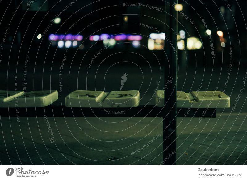 Sitzbank einer Bushaltestelle in der Stadt bei Nacht mit Lichtern Haltestelle Bank Sitzfläche LIchter Bürgersteig Straße Öffentlicher Personennahverkehr