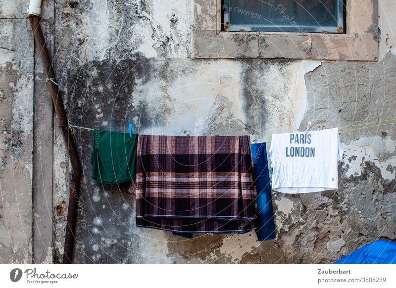 Sehnsucht - T-Shirt mit Aufschrift Paris London hängt mit anderen Wäschestücken auf der Leine vor einer alten Wand in Sizilien Wäscheleine Regenrinne baufällig
