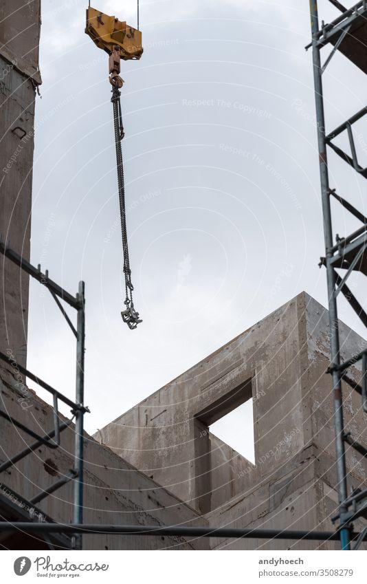 Kranhaken und Gerüst vor einem unfertigen Gebäude Appartement Architektur bauen erbaut Business Großstadt Beton Konstruktion Kranich Design Entwicklung Tür