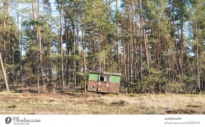 Ein Bauwagen steht am Rande eines Waldes Verlassen gealtert antik Hintergrund schön gebrochen Lager Wohnmobil Campingplatz Wohnwagen nadelhaltig Beschädigte