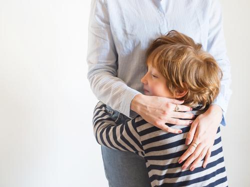 Junge Mutter und Kind umarmen sich. Tag der Mütter Mama Eltern Muttertag Frau gesichtslos Lifestyle umarmend Liebe Sohn Zusammensein Familie Emotion Gefühle