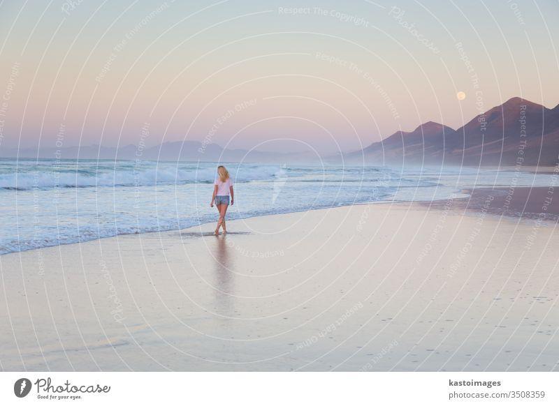 Dame beim Spaziergang am Sandstrand im Sonnenuntergang. Frau MEER Strand Landschaft Küstenlinie Fußspur Fußtritt Urlaub Wasser Natur Sommer Wellen schön Meer