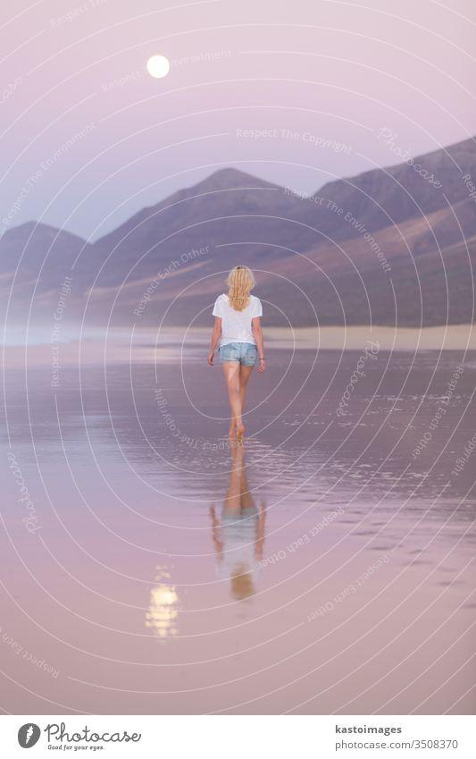 Dame beim Spaziergang am Sandstrand im Sonnenuntergang. Frau MEER Strand Landschaft Küstenlinie Fußspur Fußtritt Urlaub Wasser Natur Sommer Mondschein Wellen