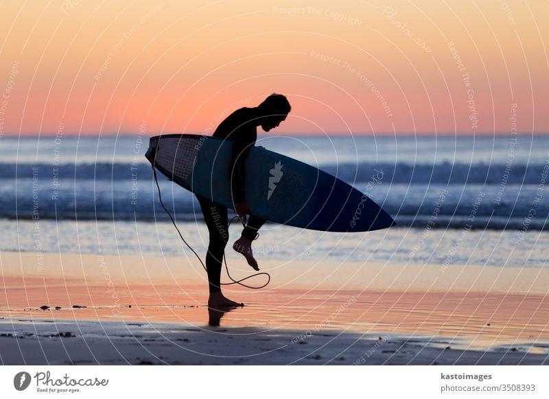 Silhouette eines Surfers am Strand mit Surfbrett. Sonnenuntergang Sommer Sport Mann Brandung Surfen Meer Wasser Natur Sonnenaufgang aktiv Spaß Holzplatte Sand