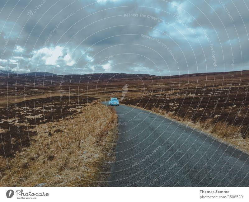 Blaues Auto fährt auf einer Straße mitten in Wicklow Mountain in Irland Wicklow-Berge Einsamkeit einsam allein blau blaues Auto PKW altehrwürdig dunkel Oldtimer
