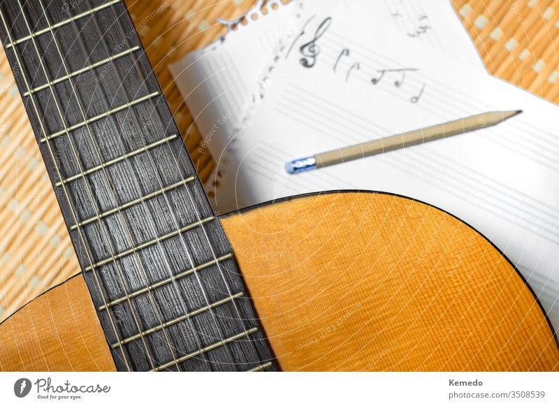 Draufsicht auf eine klassische Gitarre, Notenheft mit Notenlinien und Bleistift. Konzept des Komponierens oder Musikstudiums. komponieren Stab Musical Notebook