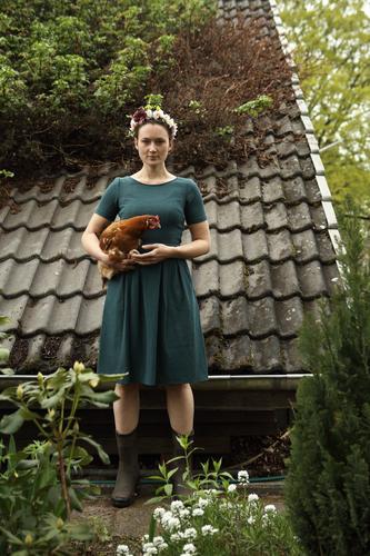 Junge Frau mit Blumenkranz im Haar steht vor Gartenhaus und hält braunes Huhn im Arm Zentralperspektive Schwache Tiefenschärfe Tag Außenaufnahme Farbfoto Idylle