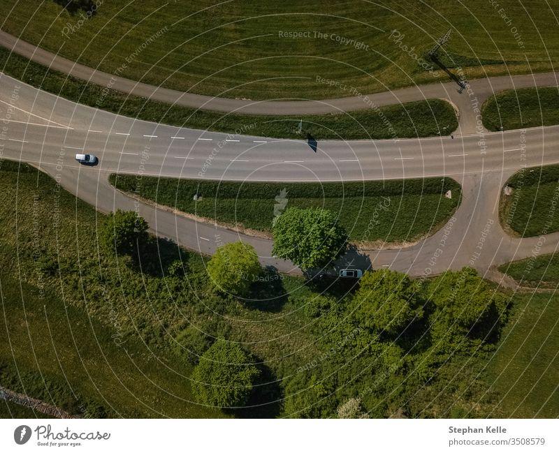 Senkrechter Blick nach unten auf eine Straße mit angrenzendem Parkplatz im Grünen. straße drohne auto von oben rasen wiese PKW grün Verkehr Landschaft Farbfoto
