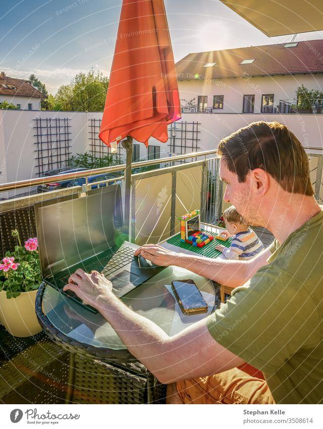 Das Innenministerium, Vater und Sohn arbeiten zusammen mit ihren Laptops zu Hause auf dem Balkon, während die Sonne scheint. Neuer Lebensstil durch Korona, Covid-19-Pandemie.