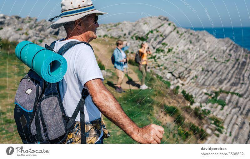 Ein älterer Mann beim Trekking mit Blick auf die Landschaft Wanderung Senior Bergmatte Rucksack Berge u. Gebirge Natur Hut Sonnenbrille rückwärts Sommer