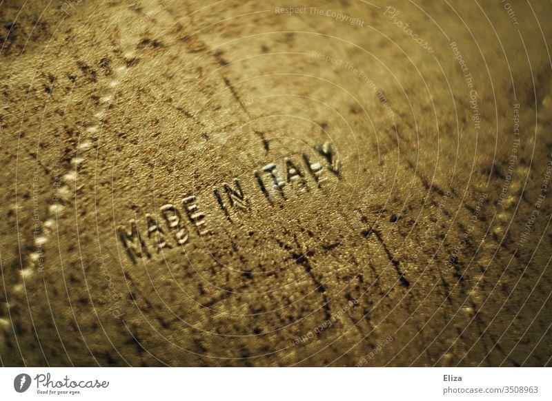 Goldener Gegenstand, auf dem Made in Italy geschrieben steht gold Struktur hergestellt in Italien Produziert produzieren Farbfoto Holz Inszenierung importiert
