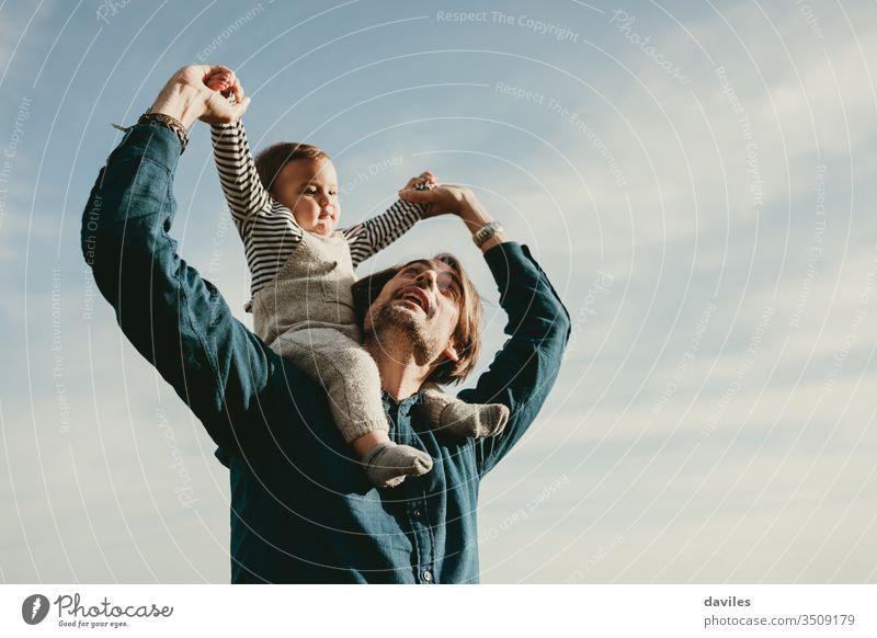 Hübscher Mann, der seinen kleinen Sohn huckepack im Freien reitet. Zusammensein schlendern Frühling Lächeln Kindererziehung wenig Fröhlichkeit Kindheit Gesicht