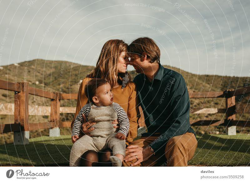 Liebenswertes Paar, das sich um seinen kleinen Sohn kümmert, mit Bergen im Hintergrund. Elternschaft Baby Junge Beteiligung romantisch umarmend Papa Mama