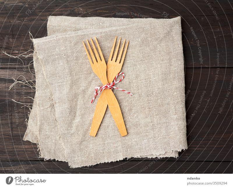 zwei Holzgabeln sind mit einem Seil zusammengebunden und liegen auf einem braunen Holzuntergrund aus Brettern Gabel selbstgemacht Haushalt Küche Küchengeräte