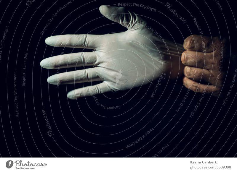 Nahaufnahme eines Heilpraktikers, der seine Operationshandschuhe vor dunklem Hintergrund ausstreckt Handschuh tragend Hände Korona Coronavirus Virus Hygiene