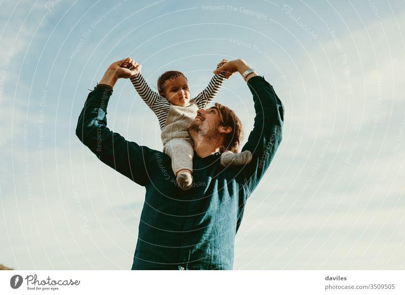 Hübscher Mann, der seinen kleinen Sohn huckepack im Freien reitet. jung Vaterschaft Waffen gutaussehend männlich Person Himmel Hintergrund niedlich weiß Blick