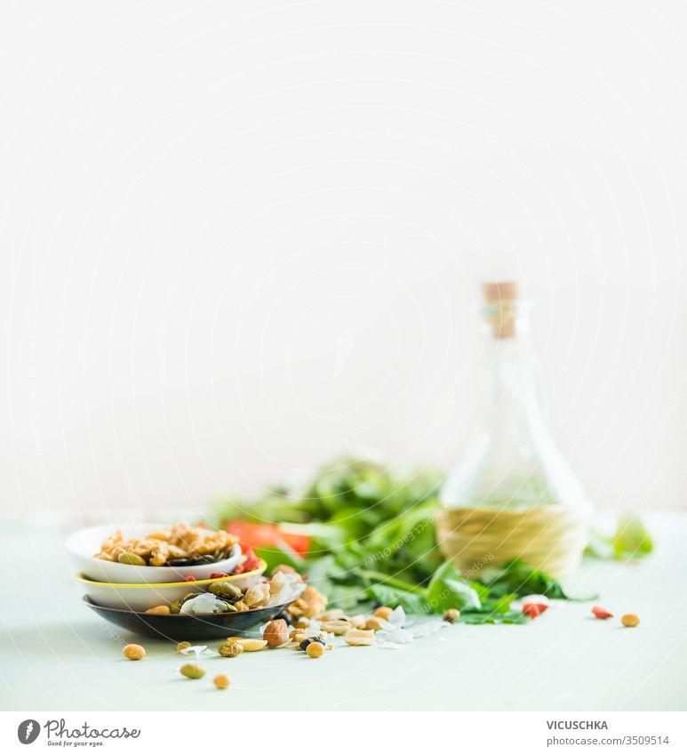 Gesunde Salatzubereitung auf weißem Tisch vor hellem sonnigen Wandhintergrund. Frische Küchenkräuter. Nüsse als Garnierung. Olivenöl. Salatdressing . Konzept für Diät oder vegetarisches Essen.