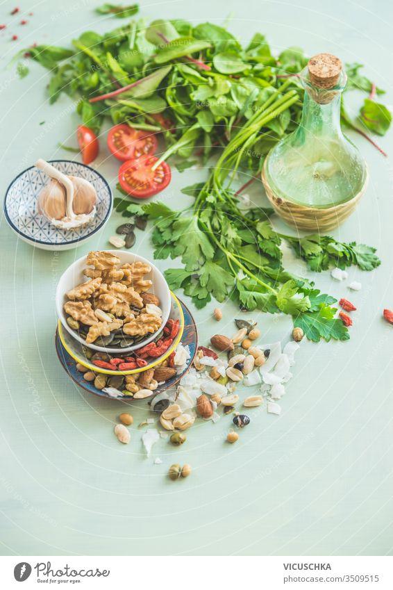 Gesunde Zutaten zur Salatherstellung. Frische Küchenkräuter. Nüsse als Belag. Olivenöle. Salatdressing . Konzept für Diät oder vegetarische Ernährung.