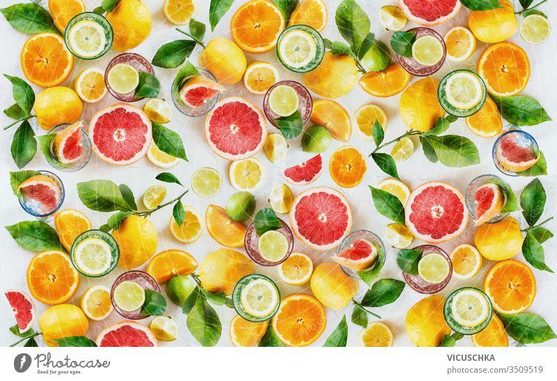 Zitrusfrüchte-Hintergrund, hergestellt aus ganzen, halben und Scheiben verschiedener Zitrusfrüchte mit grünen Blättern. Ansicht von oben. Flach gelegt. Gesunde Ernährung. Vitamine. Zutaten zum Trinken.