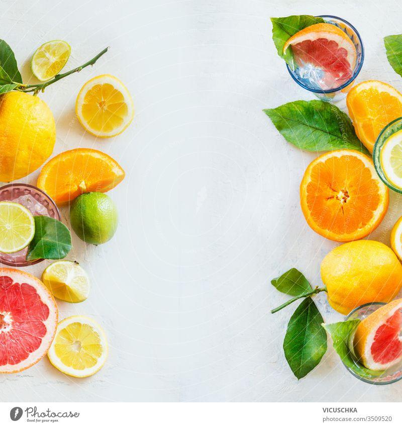 Rahmen aus verschiedenen Zitrusfrüchten mit grünen Blättern auf weißem Tisch, Draufsicht. Gesunde Lebensweise. Inhaltsstoffe. Vitamine. Hälften und Scheiben. Gestaltung