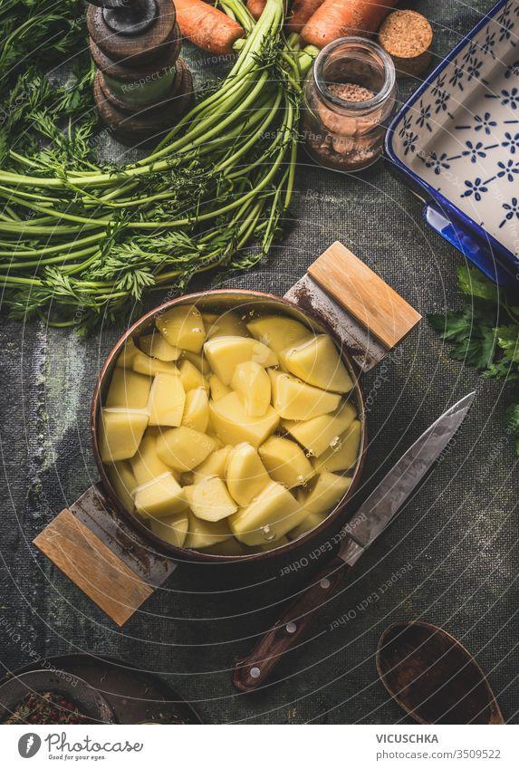 Rohe Kartoffeln in Kupferkochtopf in Wasser auf rustikalem Küchentischhintergrund. Ansicht von oben. Kartoffel-Garvorbereitung. roh kupfer Kochtopf Tisch