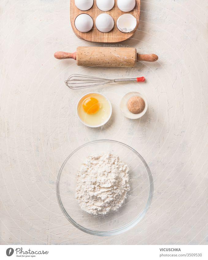 Backwerkzeuge und Zutaten für Kekse, Torten oder Kuchen auf weißem Hintergrund. Ansicht von oben. Flach ausgelegt. Mehl in Glasschüssel, Eier in Holzhalter, altes Nudelholz und Schneebesen.