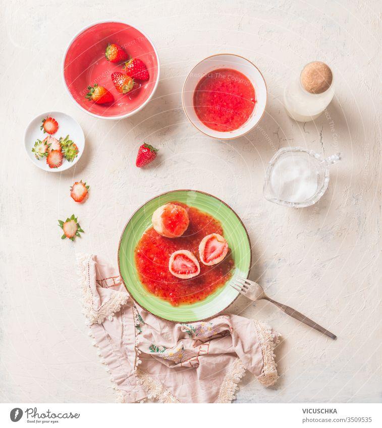 Schmackhafte gekochte Hüttenknödel, gefüllt mit frischen Erdbeeren. Sommersüßes Essen. Frühstück geschmackvoll Cottage Knödel erdbeeren Beeren Saucen grün