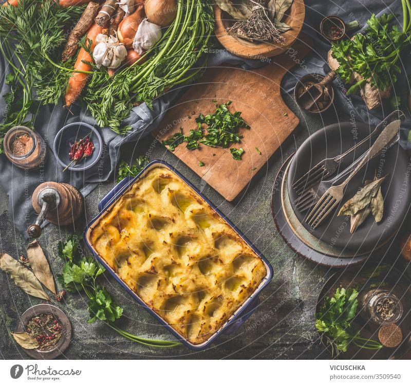 Gebackenes Kartoffelpüree in Kasserolle mit Löffel auf dunklem rustikalem Küchentischhintergrund mit Zutaten und alten Utensilien. Ansicht von oben. Schmackhafte Hausmannskost