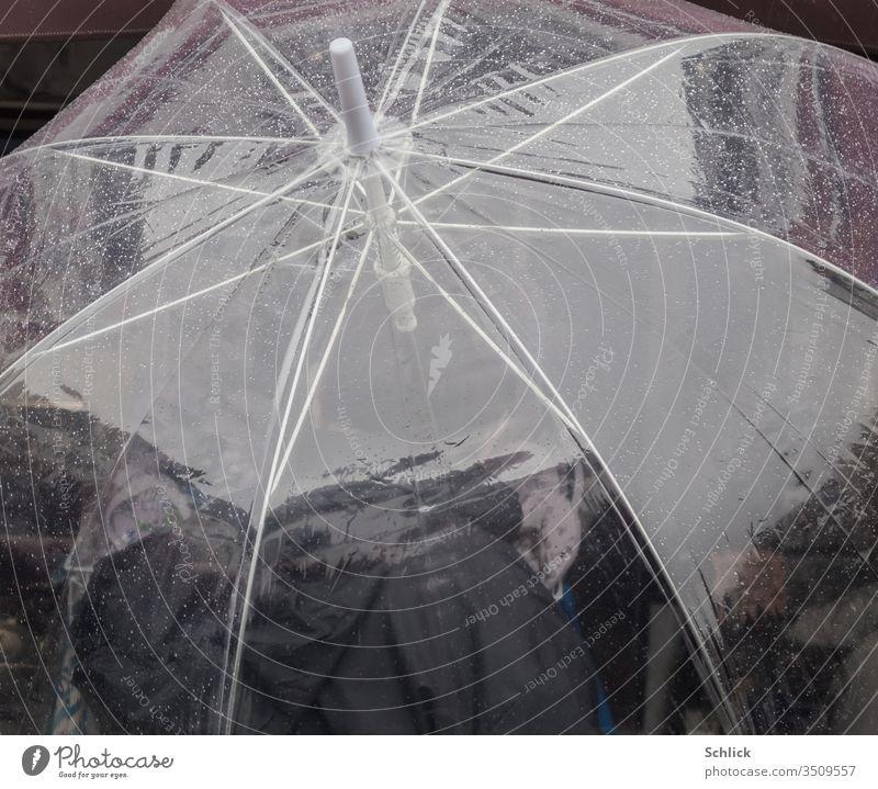 Transparenter Regenschirm mit Regentropfen von schräg oben fotografiert transparent Wassertropfen durchsichtig Mensch Person Polyurethan Kunststoff Folie