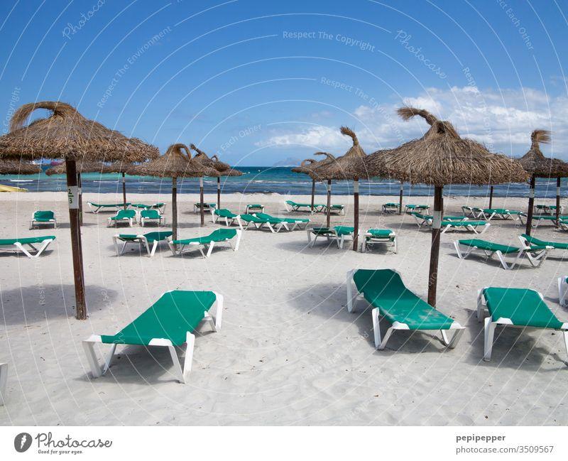 leerer Strand mit grünen Sonnenliegen und braunen Sonnenschirmen Sonnenschirmständer Ferien & Urlaub & Reisen Meer Sommer Himmel Sand blau Außenaufnahme