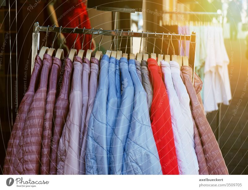 Kleiderständer mit Steppjacken für Damen, die vor dem Geschäft hängen Damenbekleidung Mode Kleidung steppjacke Bekleidung Jacke Frühling Laden Werkstatt Anzeige