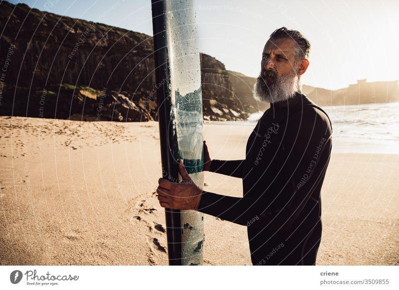 älterer Mann mit langem Bart trägt Surfbrett am Strand Senior Männer Urlaub Surfen Erwachsener Stehen graue Haare Lifestyle Beteiligung Sport Hobby Porträt