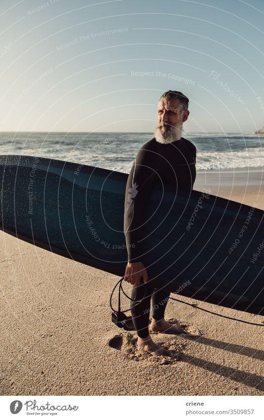 Lächelnder älterer Mann mit Surfbrett am Strand Senior Männer Urlaub Surfen Erwachsener graue Haare Lifestyle Freude Sport Hobby Porträt Vollbart Brandung Meer