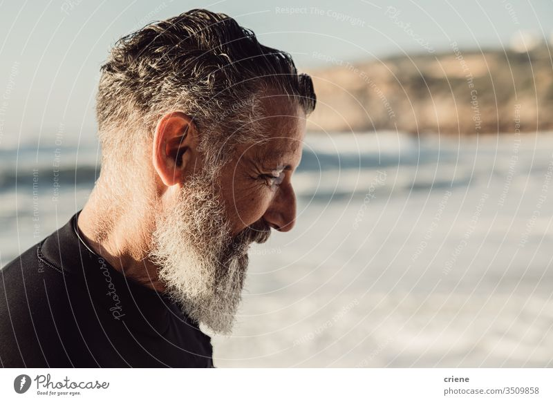 Älterer Mann mit langem Bart lächelt am Strand Senior Männer Urlaub Surfen Erwachsener Lächeln graue Haare Lifestyle Freude Sport Hobby Porträt Vollbart