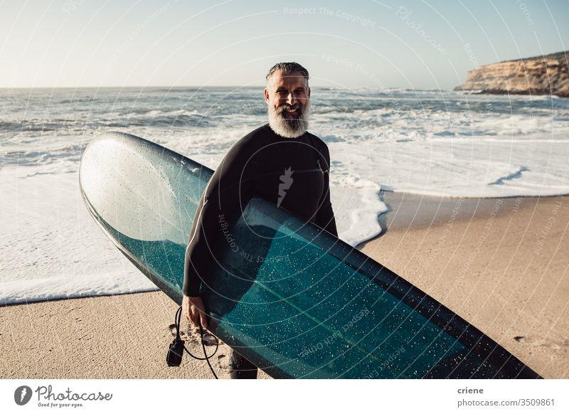 Lächelnder älterer Mann mit Surfbrett am Strand, der in die Kamera schaut Glück Senior Männer Urlaub Surfen Erwachsener graue Haare Lifestyle Freude Sport Hobby